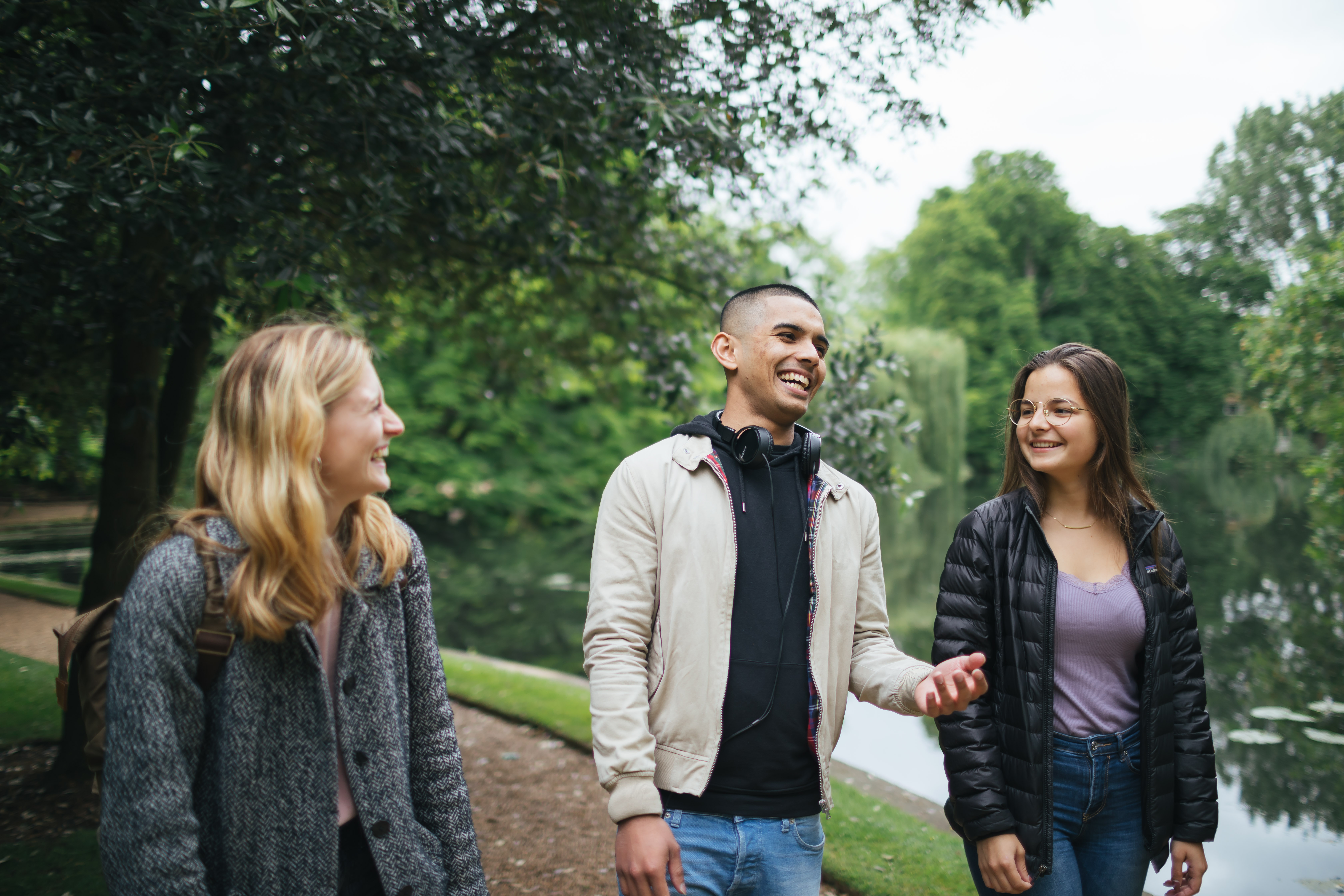 Three students laughing while walking next to Worcester College lake