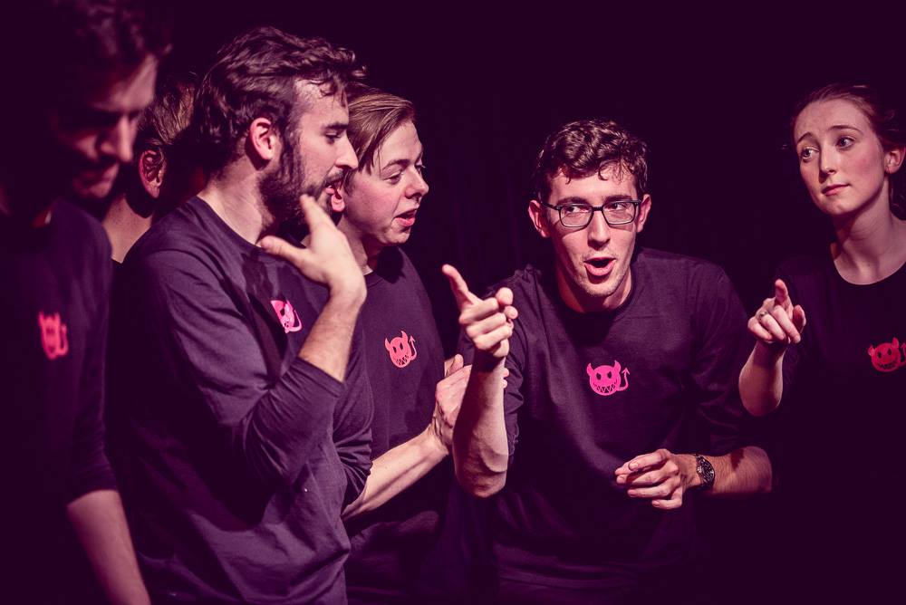 A group of the 'Oxford Imps' improv comedy troupe performing together on stage