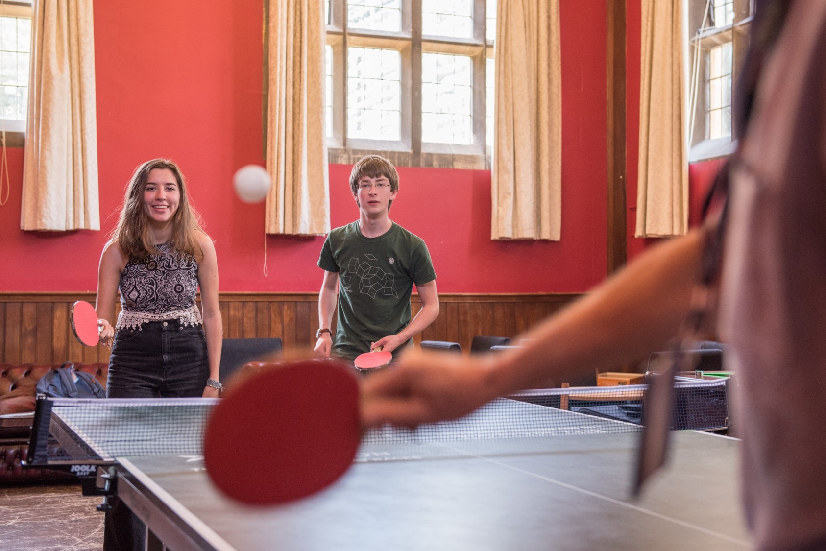 Three students playing table tennis in a large room with red walls