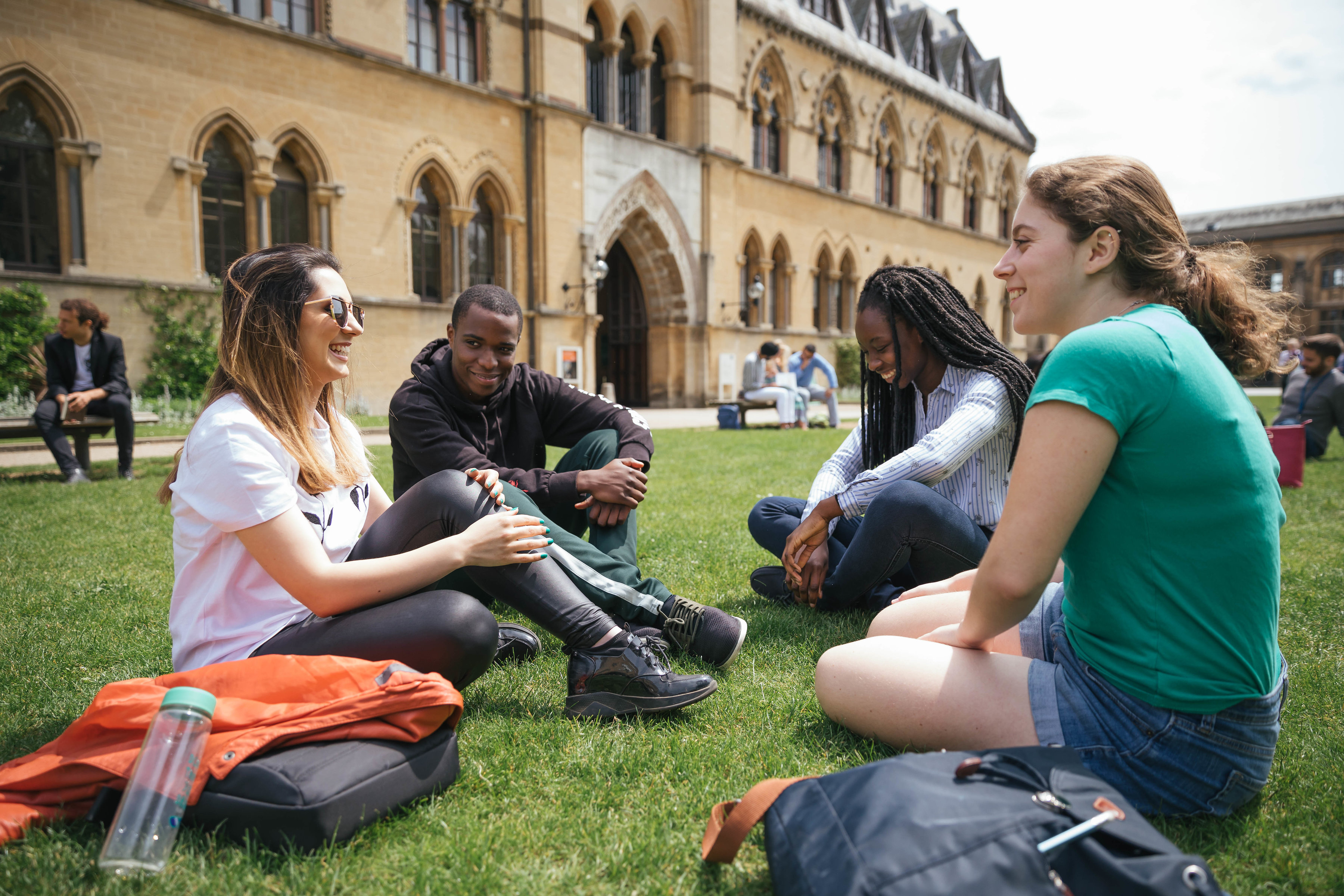 Four students sat chatting on the grass outside the Oxford Museum of Natural History