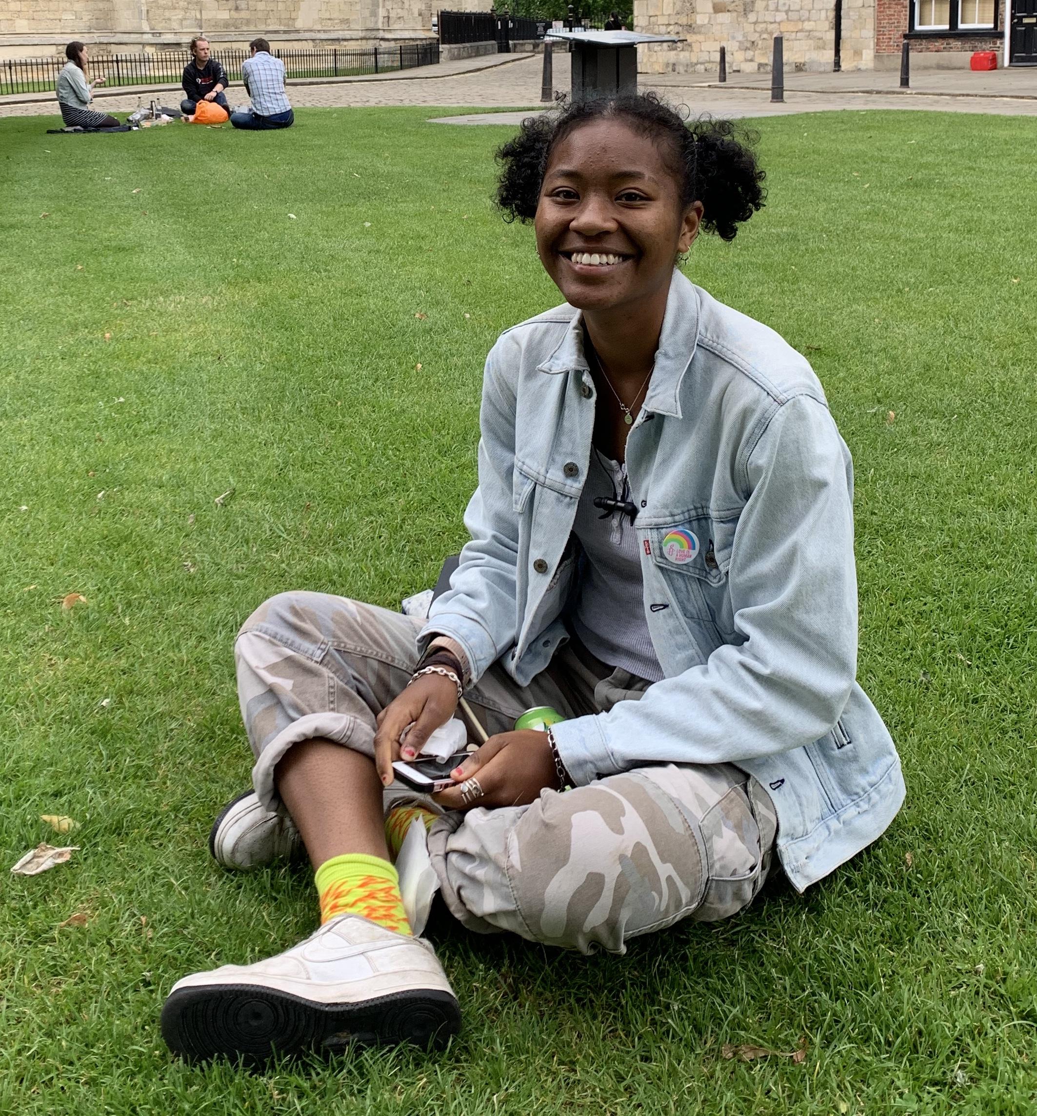 Student sat cross-legged on grass
