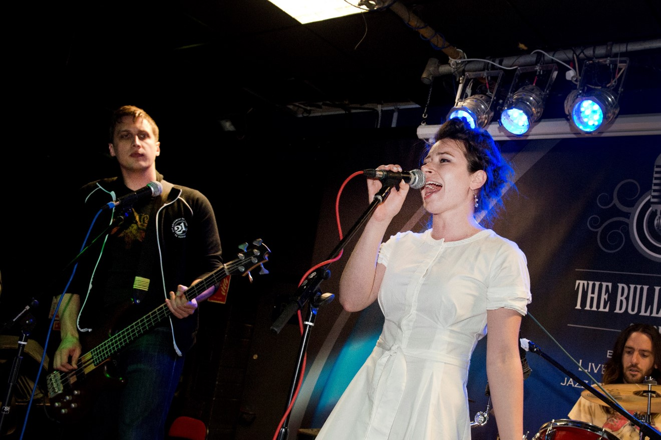 A singer performing with a live band at a music venue in Oxford