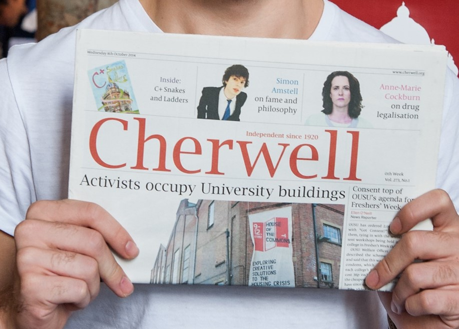 A student holds a copy of the Cherwell student newspaper up in front of them