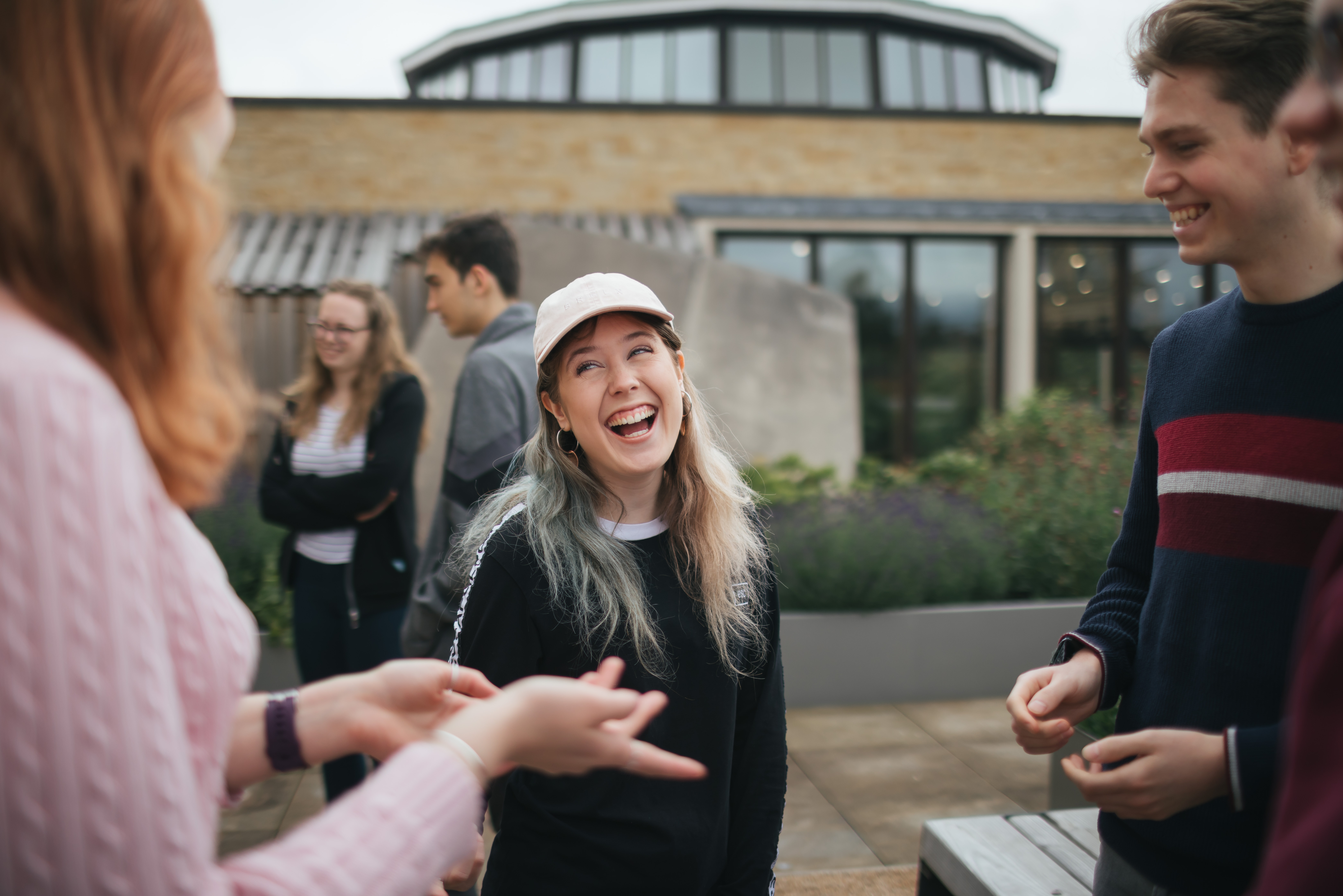 Three students laughing on the roof terrace of St Anne's College
