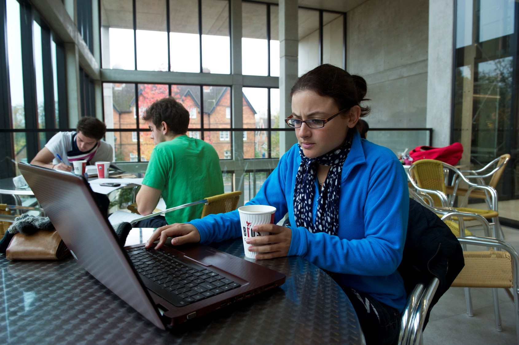 A student working on a laptop, at a metal café table with a paper hot drink cup