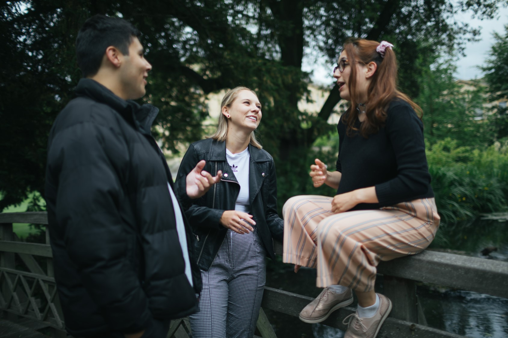 Three students talking on the wooden bridge over the Worcester College lake