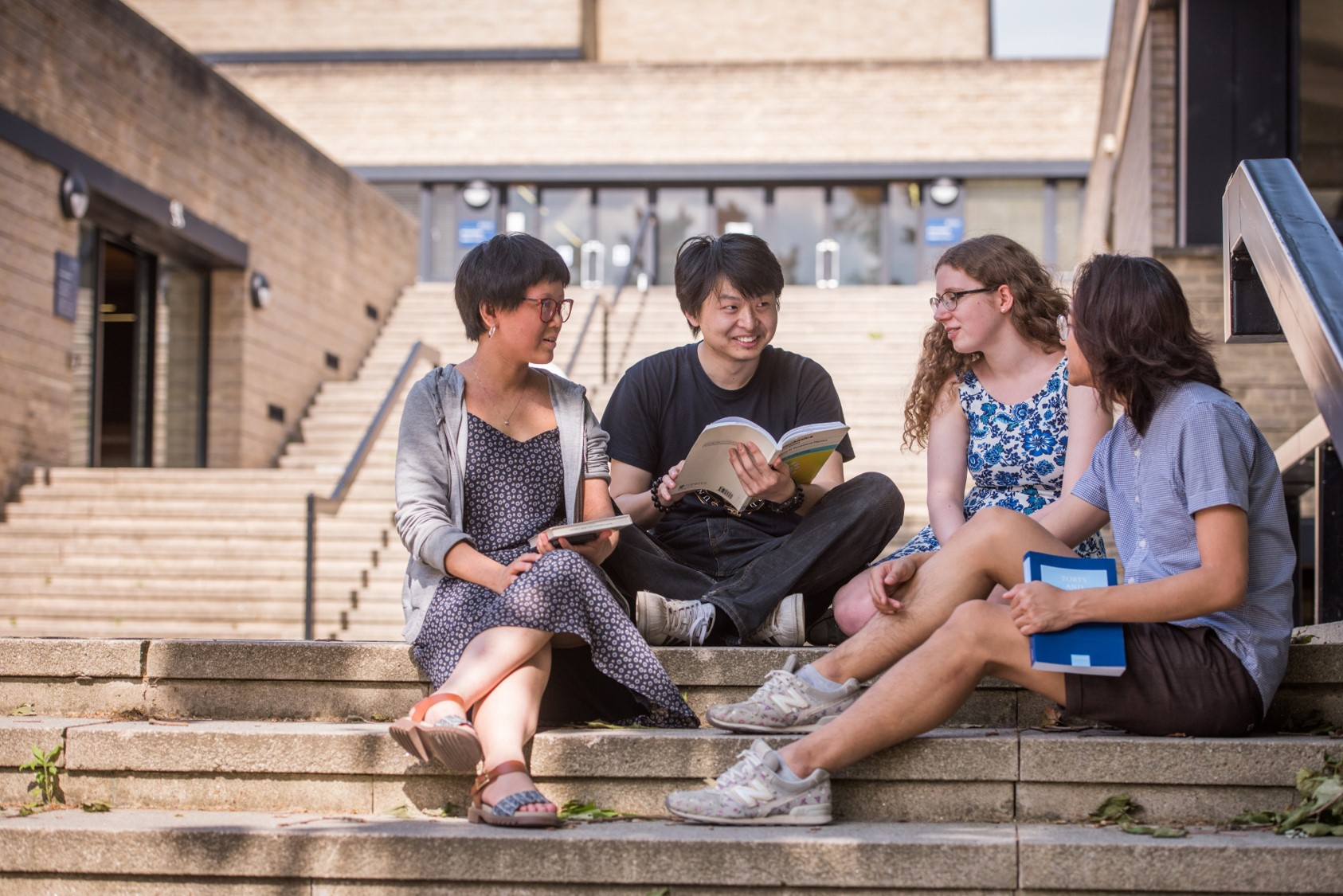 Four students sitting on the steps outside the English Faculty library