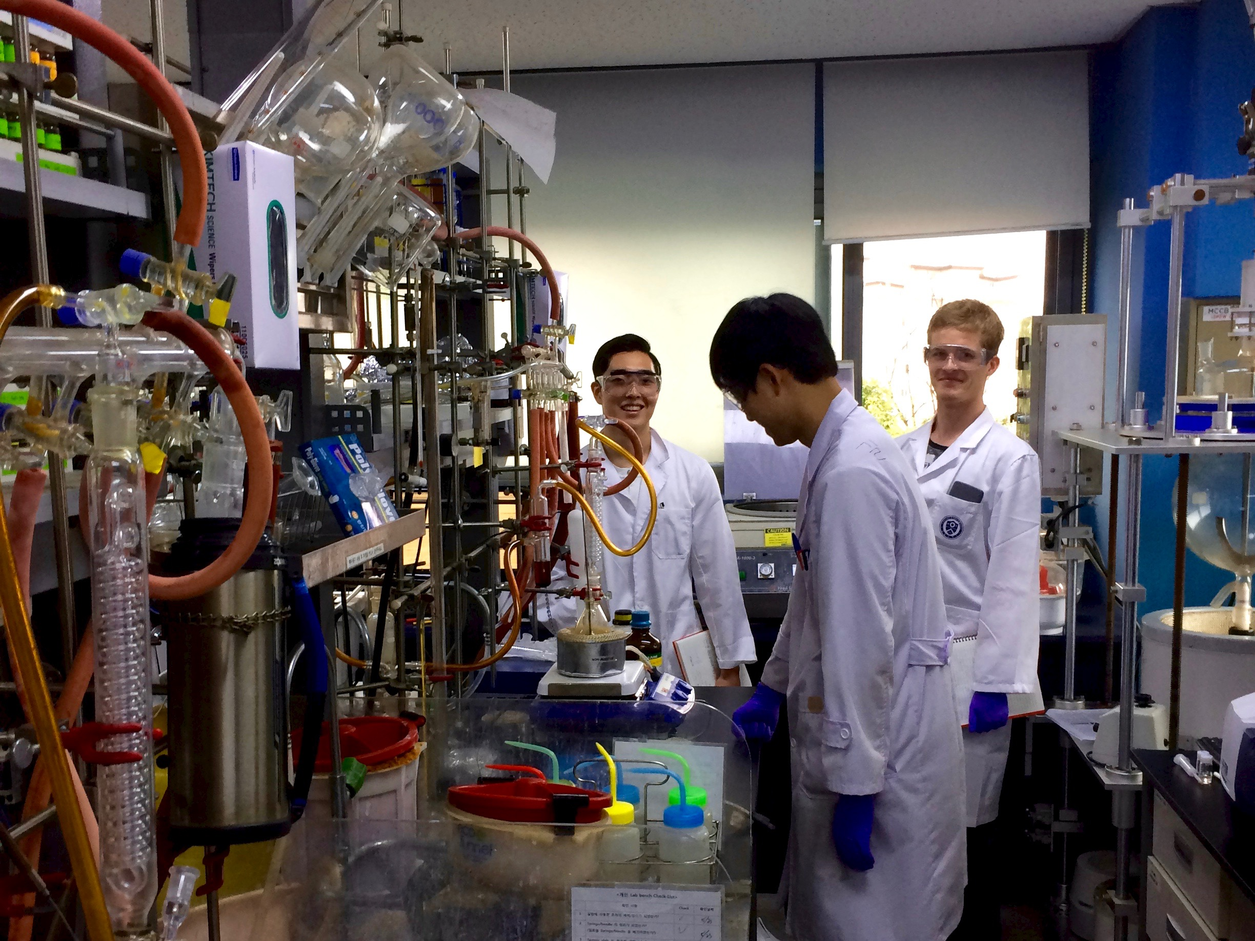 Three students in lab coats conducting an experiment