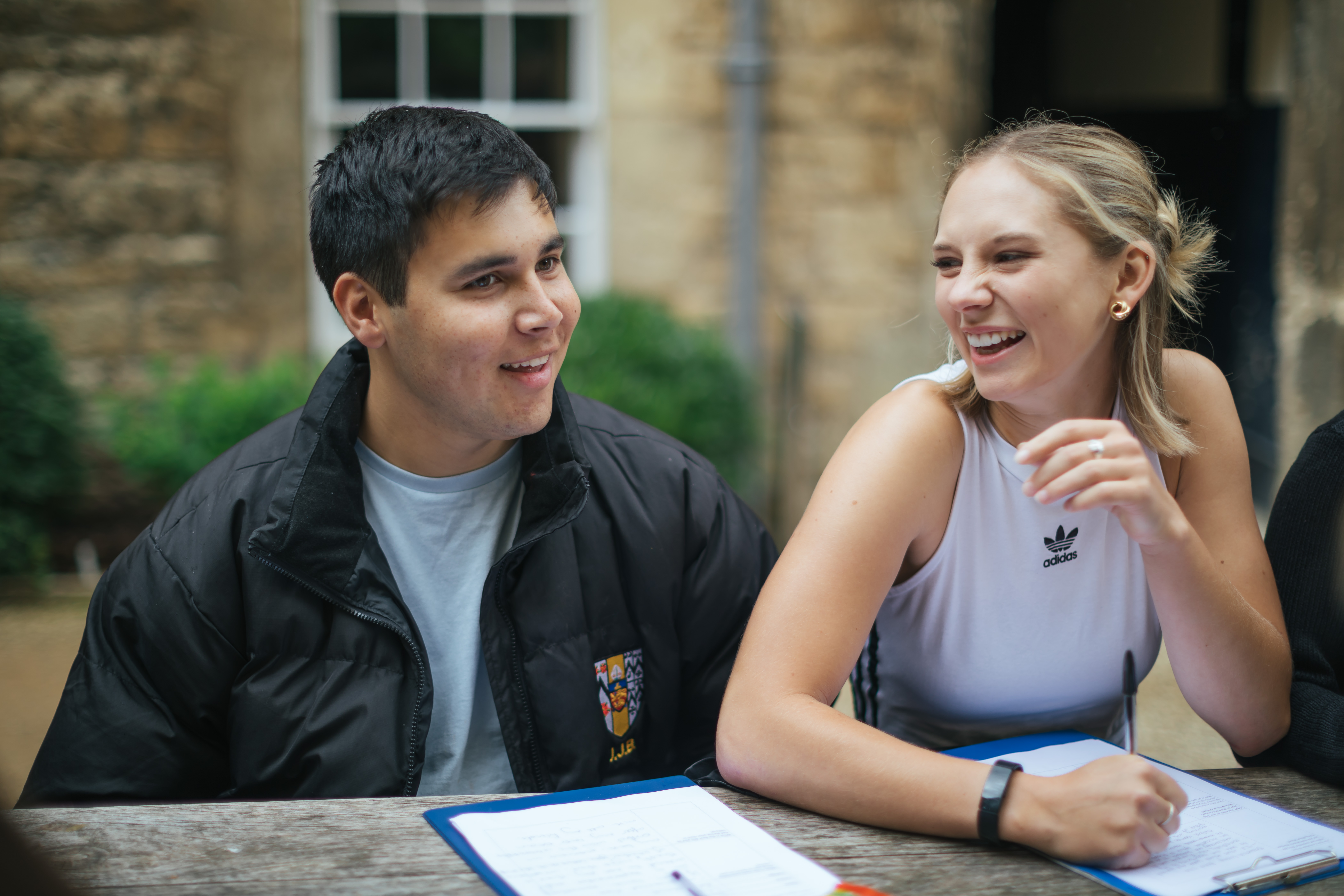 Two students laughing while filling in forms in the courtyard outside Worcester College bar