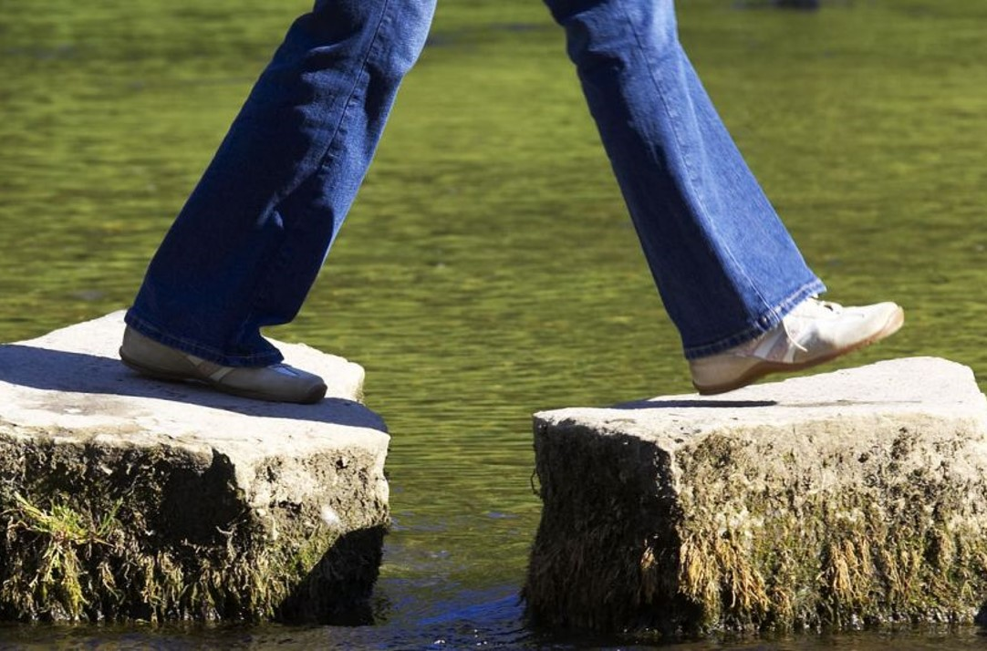 Feet walking across two stepping stones in some water