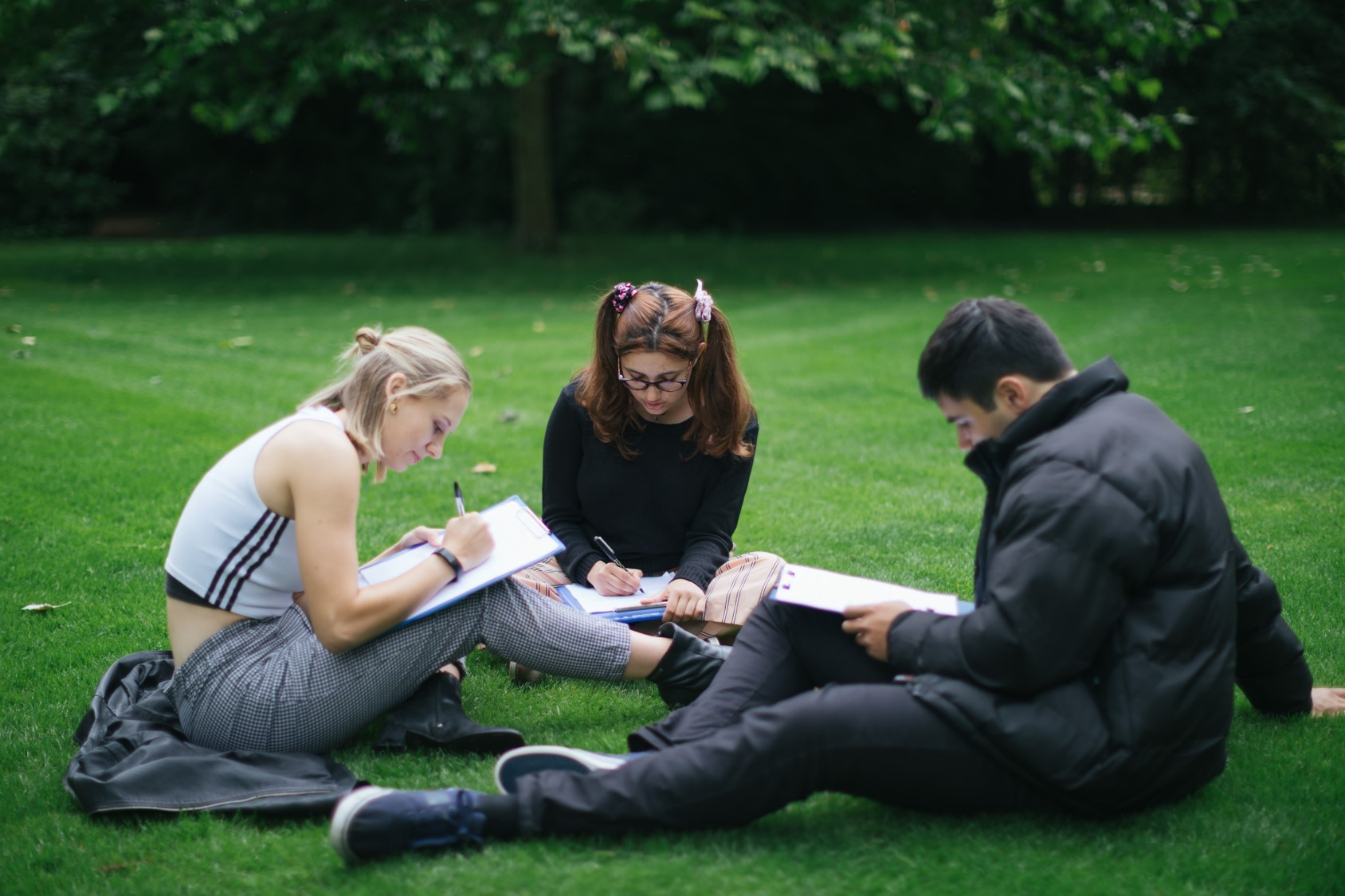 Three students writing while sat on the grass in Worcester College