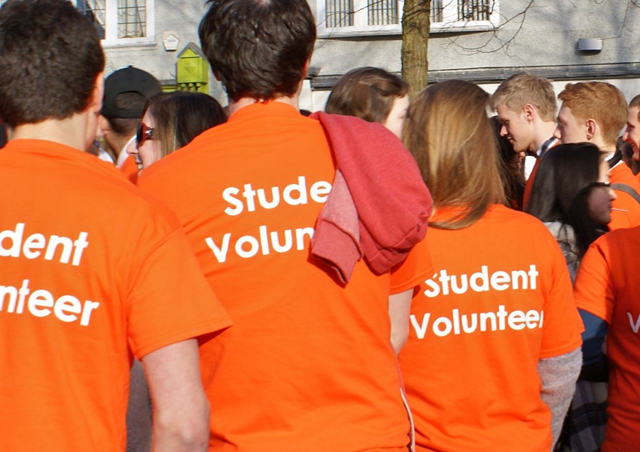 A group of students in bright orange t-shirt which say 'Student Volunteer' on them gather in central Oxford