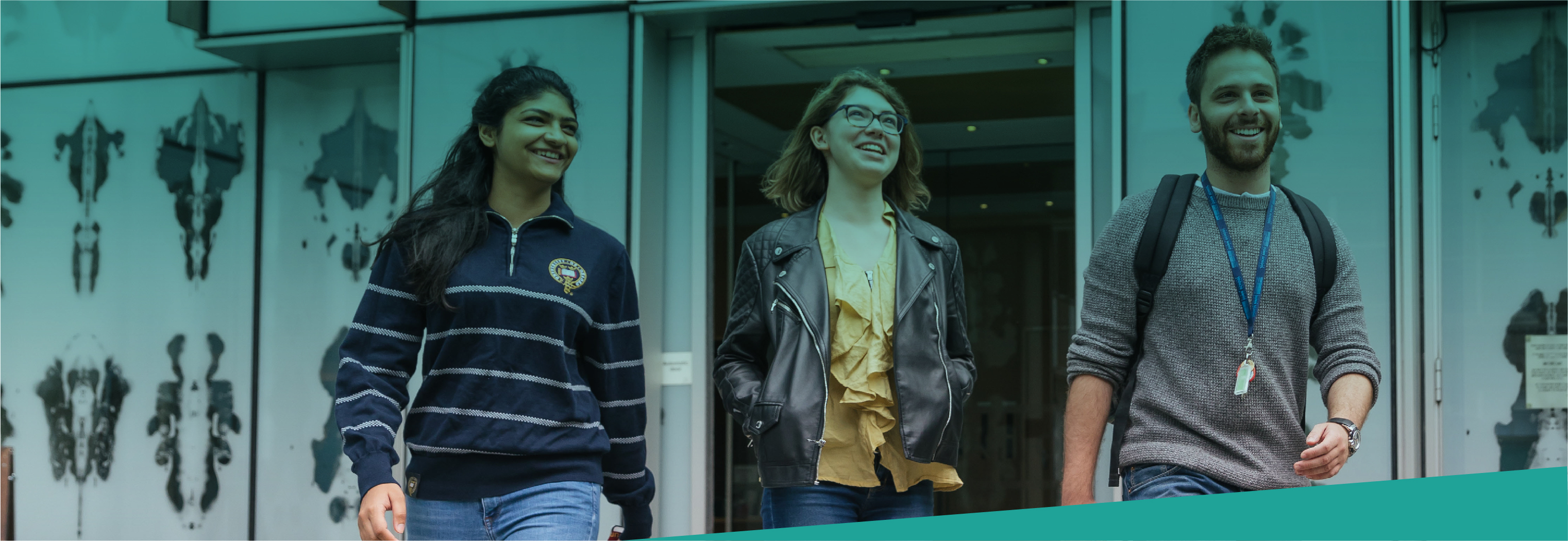 Three students walking in front of Biochemistry building
