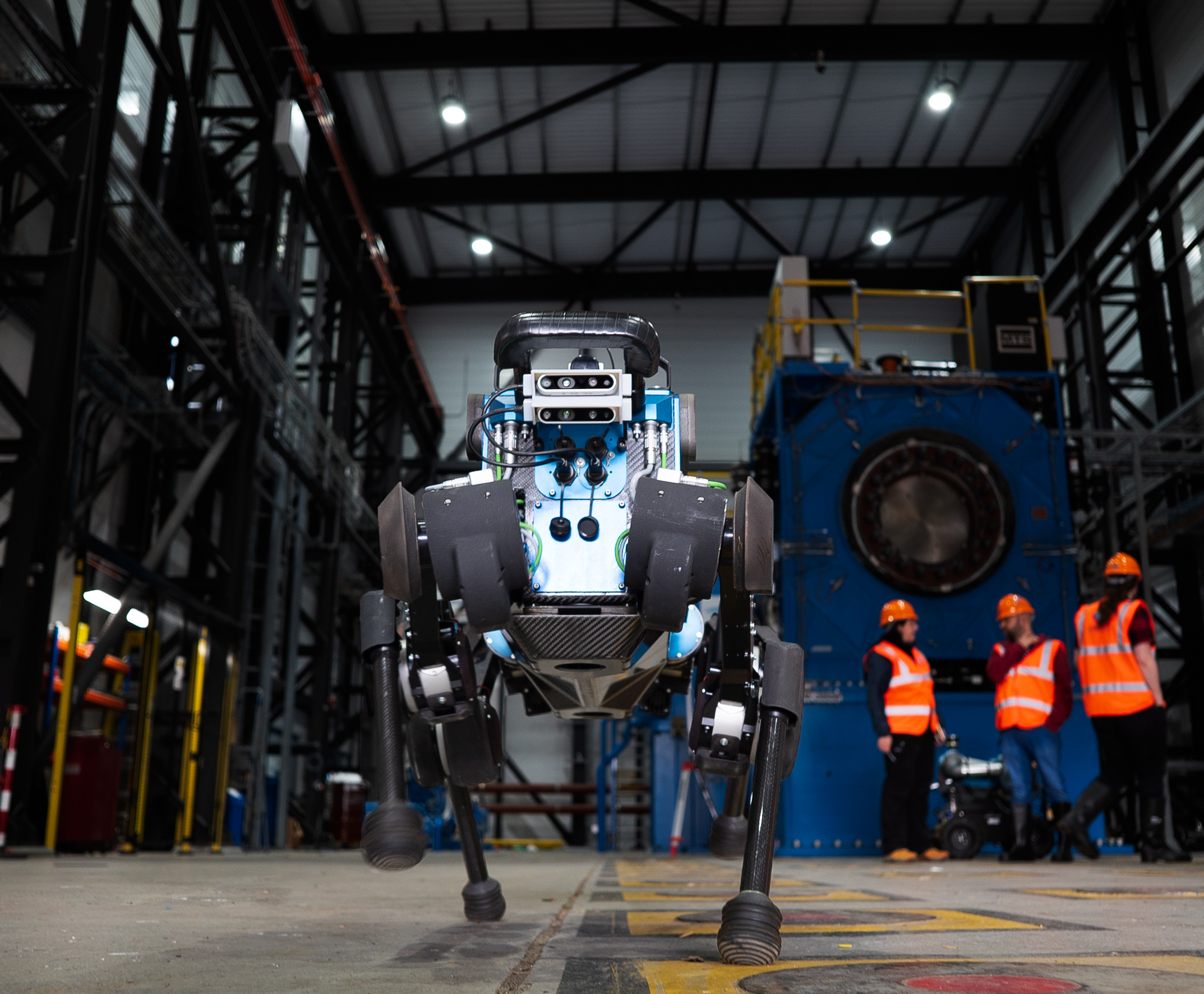 Autonomous robot in a warehouse with three people in hard hats and hi-vis vests