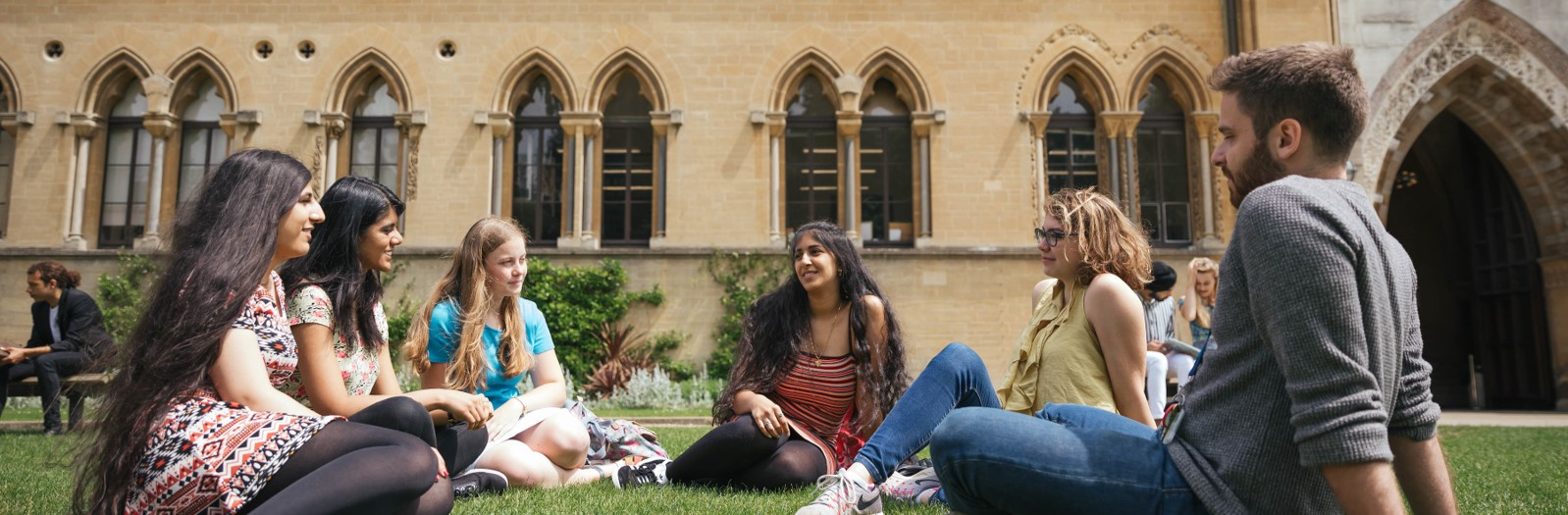 A group of student relax on the grass outside the Natural History Museum