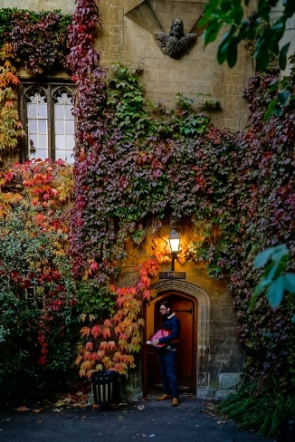 A secluded doorway at Balliol College covered with beautiful autumnal foliage.