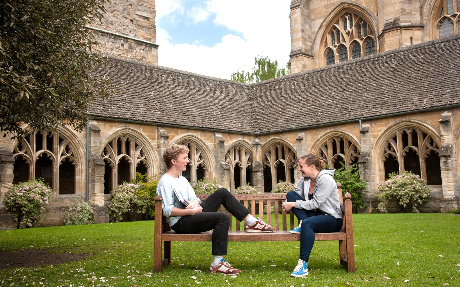 Students sit in New College cloisters