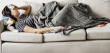 Woman laying on the couch sick with flu