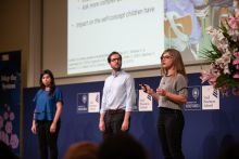 Three students speaking at the Map the System competition