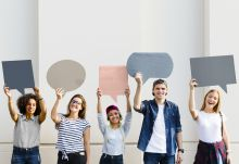 A mixed group of five students holding cut out speech bubbles