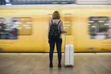 Woman waiting for a train, holding a suitcase