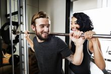 Two students using a barbell machine
