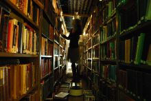 A woman searches for a book in a library