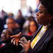 A conference delegate poses questions to the presenter. In the background is a blurred sea of other delegates' faces watching her as she speaks.