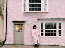 A wooman in a pink coat stands in front of a pink house