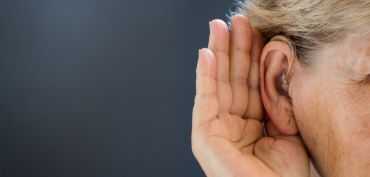 Photo | Elderly woman with hearing aid on grey background. Close up.