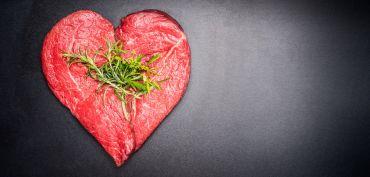 Photo | Heart shape raw meat with herbs on dark chalkboard background
