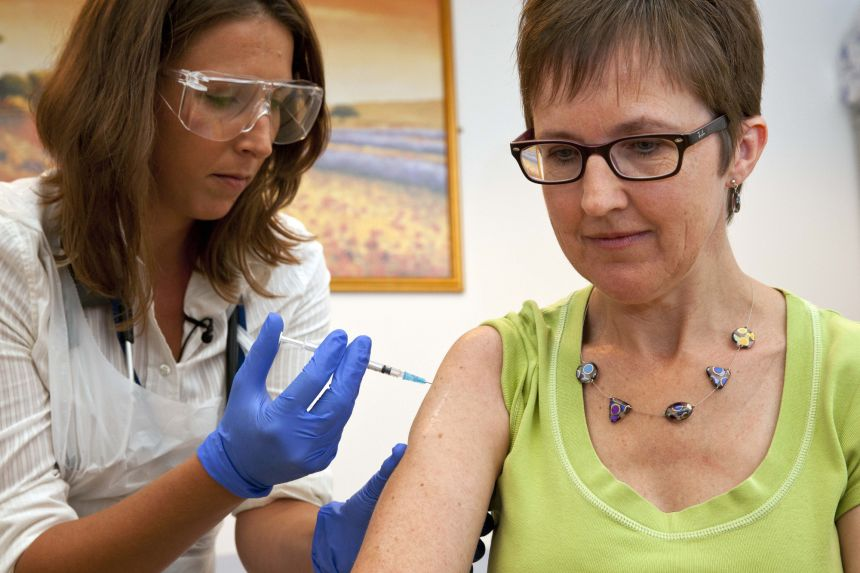 Dr Felicity Hartnell injects Ms Ruth Atkins with the Ebola vaccine