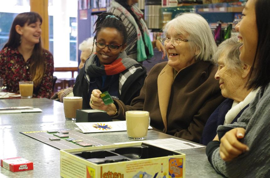 LinkAges volunteers and their elderly companions visit a local board game café