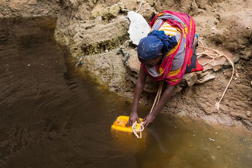 Woman takes water from a well