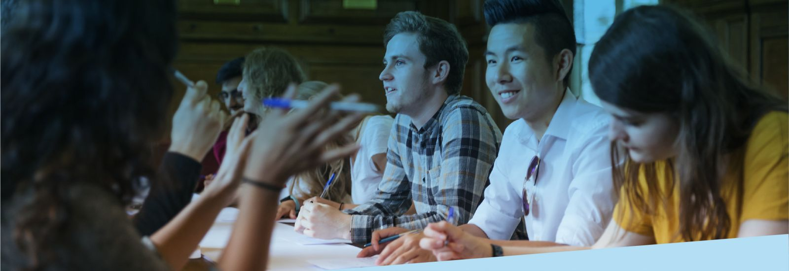 A large group of students chatting while writing in a college dining hall