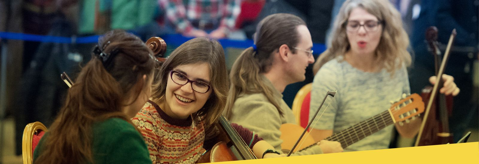 Three students sat with string instruments and one with a guitar prepare for a concert