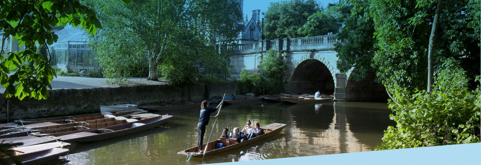 A group of punts moored and one being punted down the Cherwell River next to the Botanic Garden