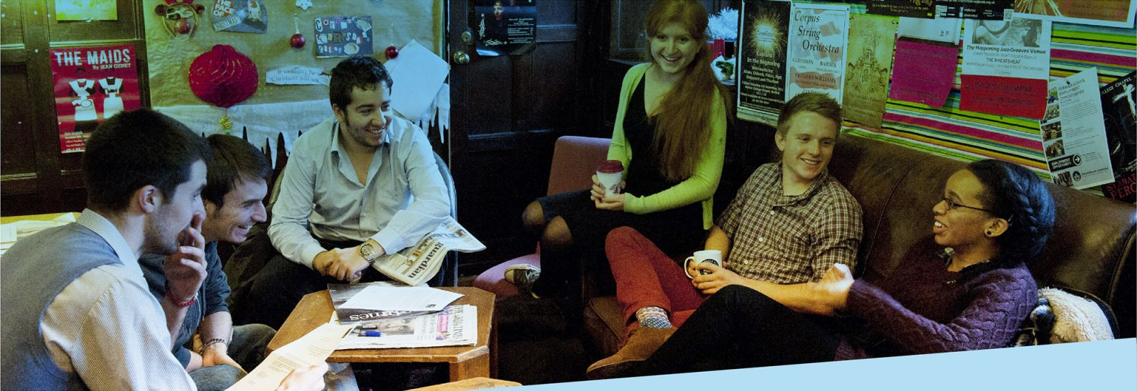 Six students sitting on sofas in a wood panelled common room surrounded by posters