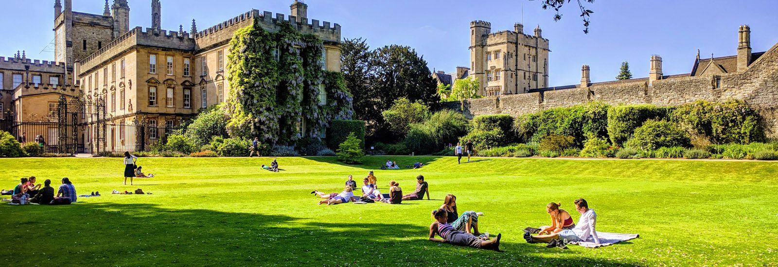 Students on the grass in the grounds of New College