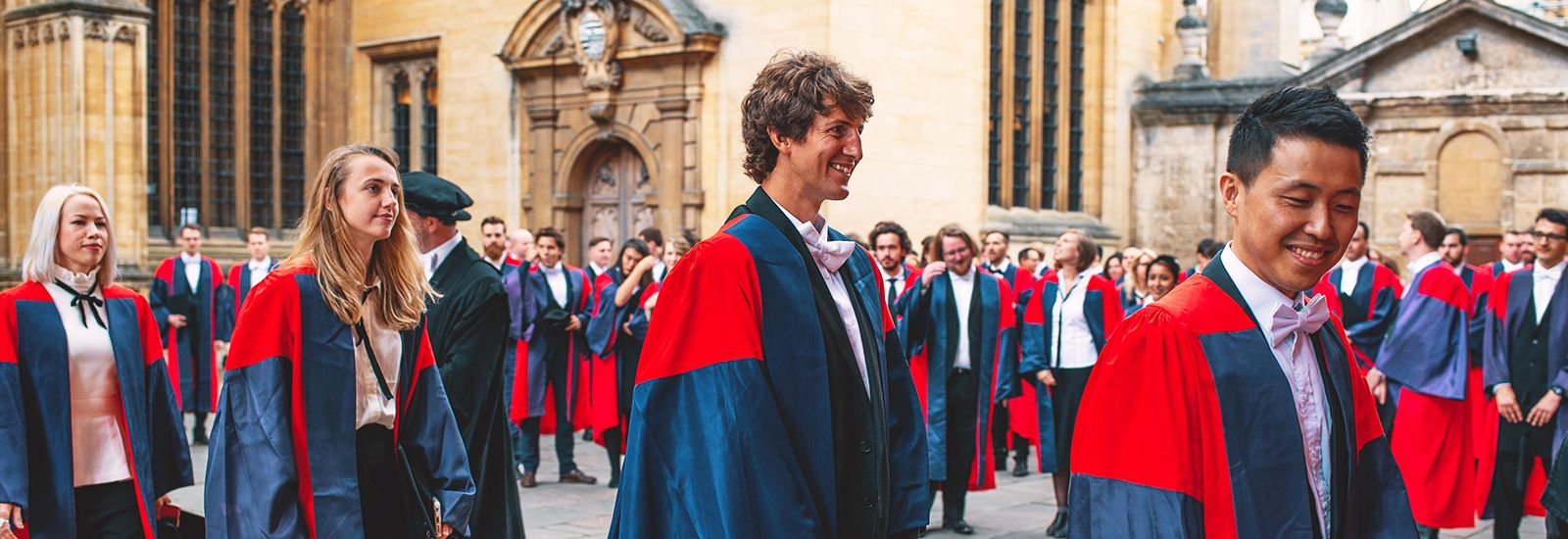 A photo of DPhil graduands wearing red and blue robes outside the Sheldonian Theatre