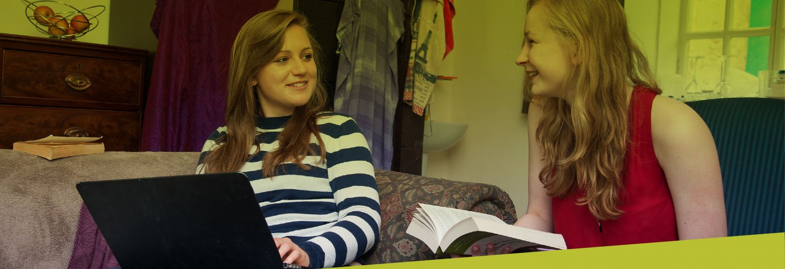 Two students working together in a college bedroom