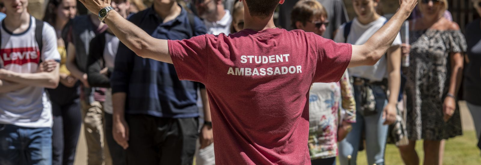 Student ambassador with his arms outstretched