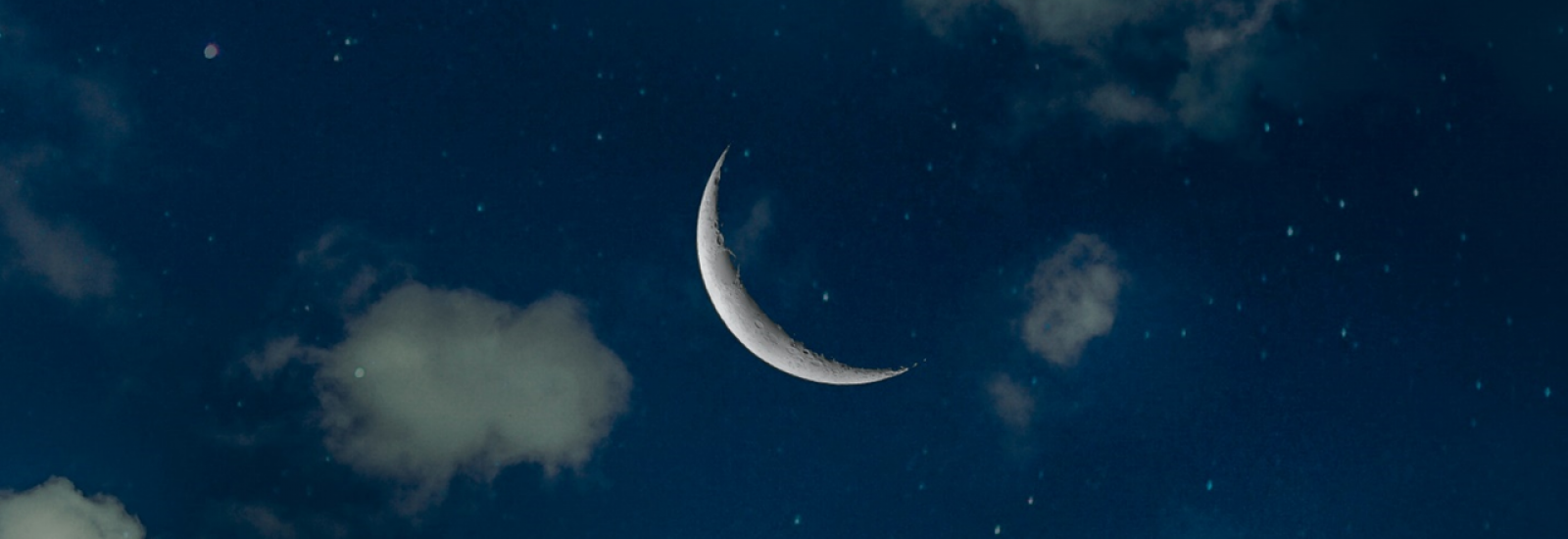 Crescent moon against indigo sky and clouds