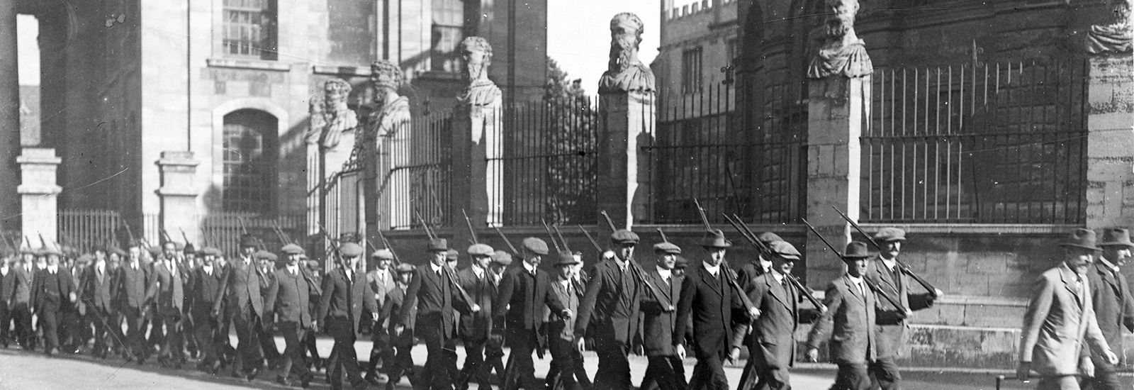 A black-and-white photo of Godley's Own Oxford volunteers marching past the Sheldonian Theatre