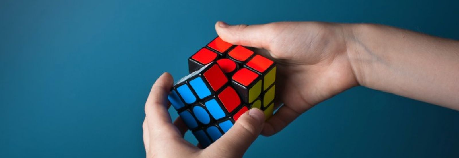 Hands twisting a Rubik's Cube, with completed blue and red sides visible