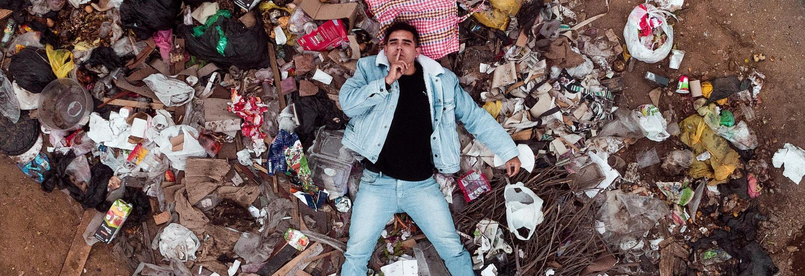 Overhead photo of man lying on a pile of rubbish