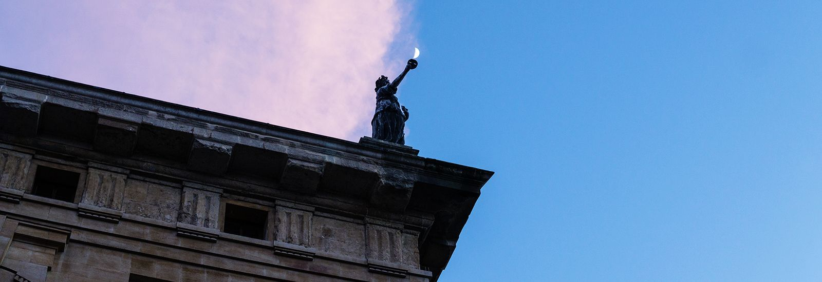 A statue on the corner of the Clarendon Building at dusk