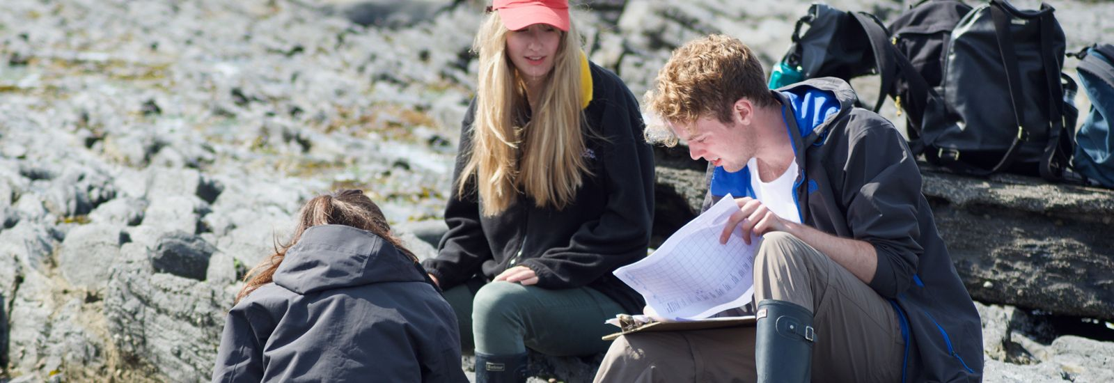 Three students in outdoor clothes record data on a clipboard in a rocky area of Orielton, Wales