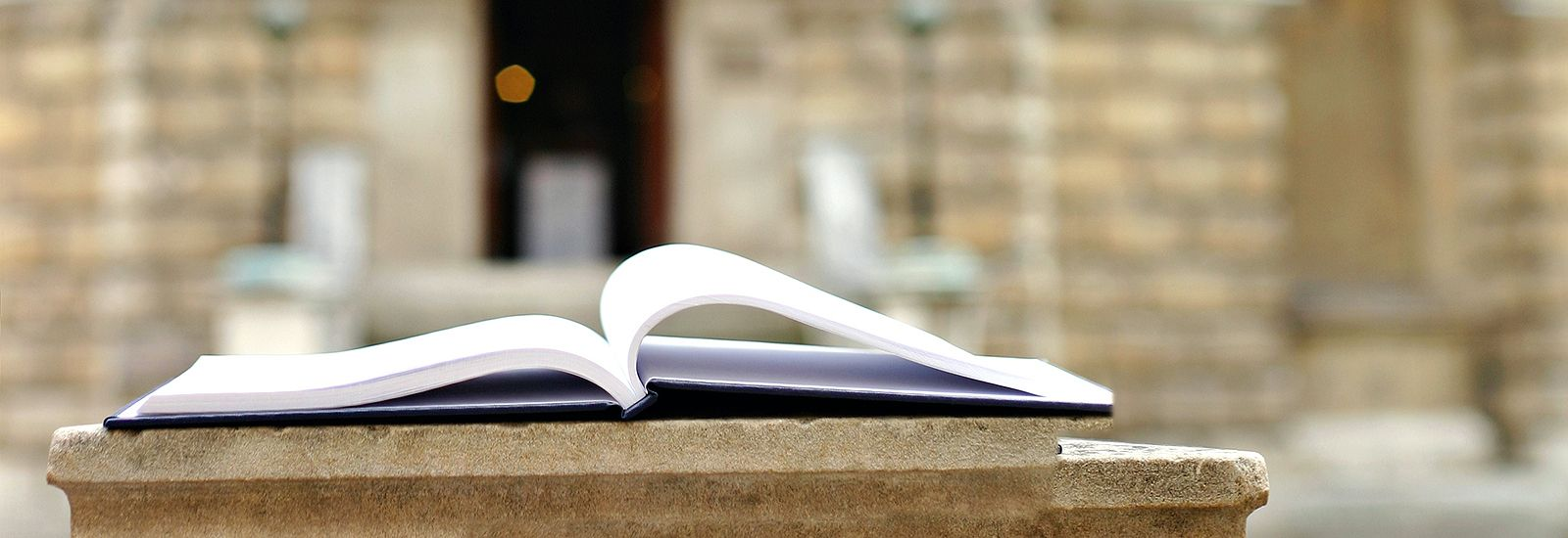 Side view of an open book with the Radcliffe Camera in the background