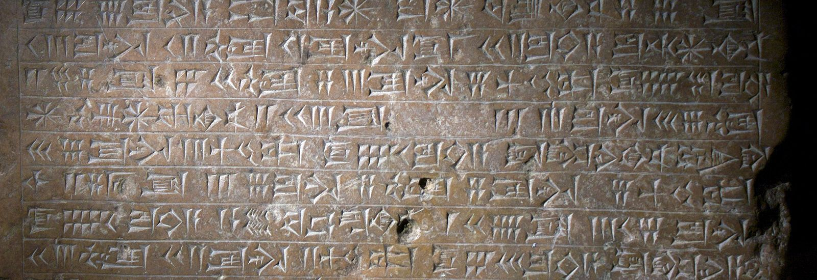 A close up of cuneiform engraved into a stone tablet